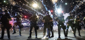 Photo depicting police waring riot gear at a rally with sparks flying