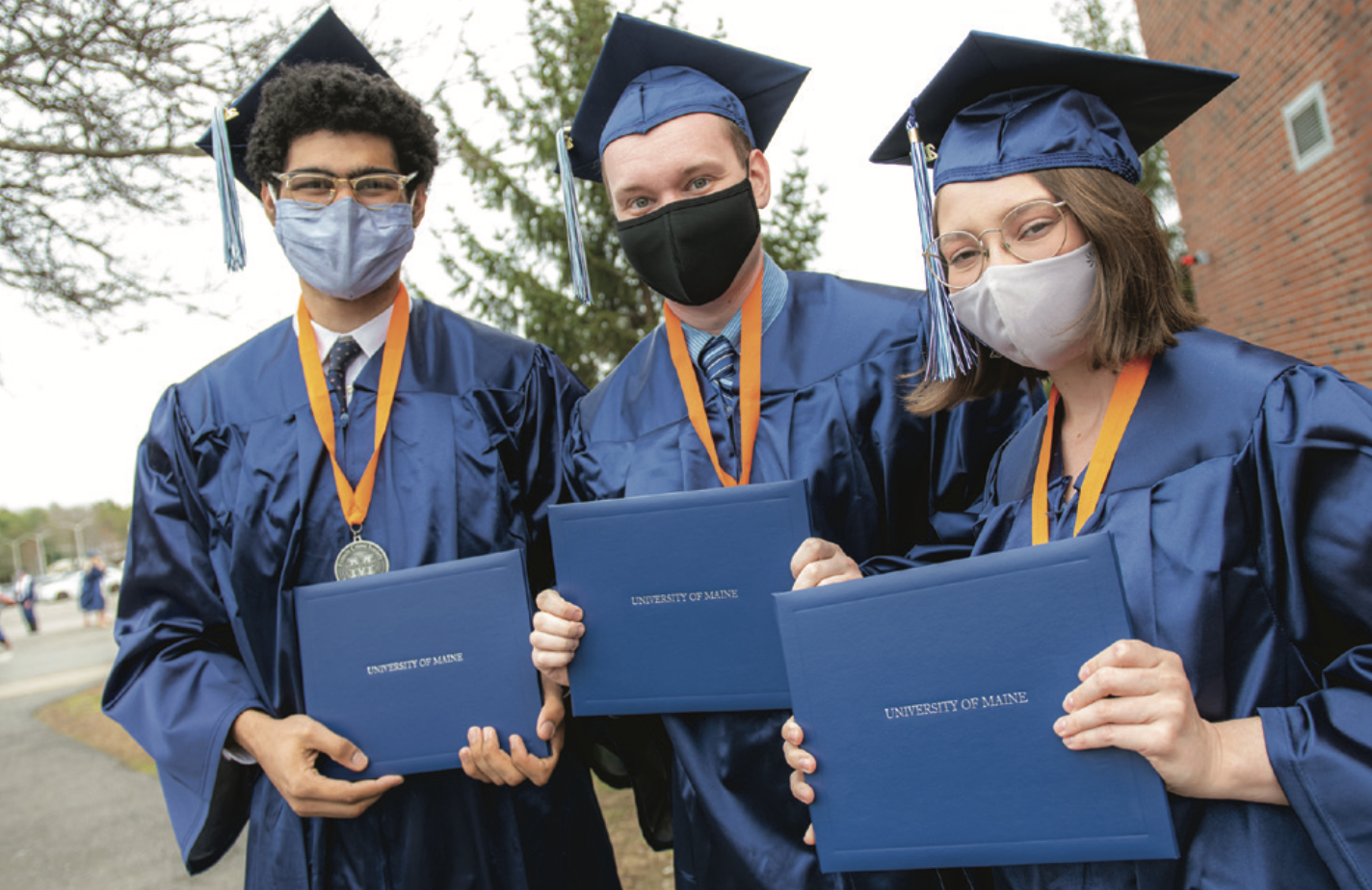 Three members of the graduating class holding up their University of Maine diplomas.