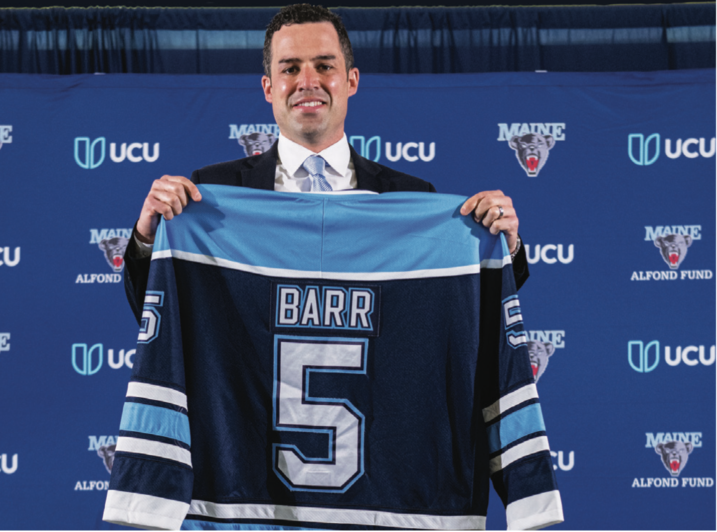 """Ben Barr holding up a #5 jersey that reads """"BARR"""" over the number"""